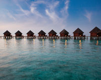 Island in ocean, overwater villas at the time sunset.Sea tropical landscape in a sunny day Stock Photos