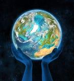 Island på planetjord i händer Royaltyfria Bilder