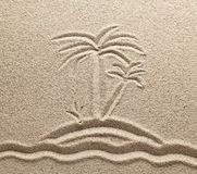 The island with palm trees in the sea is drawn on. River sand Stock Image