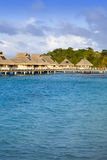 Island with palm trees and small houses on water in the ocean Royalty Free Stock Photos