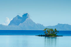 Island with palm trees in the South Pacific. View of an island with palm trees in the South Pacific Ocean with Bora Bora in the distance Royalty Free Stock Photography