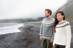 Island par som bär isländska tröjor på stranden arkivfoto