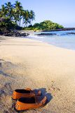 Island Peace. Leather shoes handmade in Positano Italy sitting on a white sandy beach in Kona Hawaii. Quiet,peaceful setting with palm trees, black lava rock and stock photo
