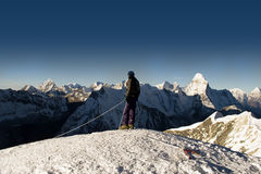 Island Peak Summit - Nepal. Mountaineer on the summit of Island Peak, Nepal. Ama Dablam is in the background stock images