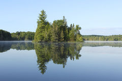 Island Reflection. Island and Mirror Reflection on the Surface of a Lake - Haliburton, Ontario, Canada royalty free stock images