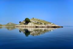Island. Reflection of small island in calm sea in National Park Kornati, Adriatic Sea, Croatia royalty free stock photo