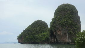 Island with rocks in the azure sea near the beach. In tropic in cloudy weather stock video