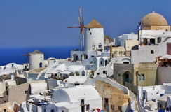 The island Santorini in Greece. Attractive view. White houses and windmill, sea. Sunny day Stock Photo