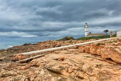 Island scenery with rocks and sea in gloomy weather, lighthouse. At Cap de Ses Salines on Majorca, Spain Mediterranean Sea royalty free stock photos