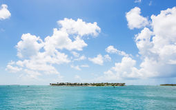 Island. Scenic island in deep blue water, with blue sky and clouds Stock Photography