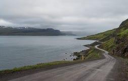 Island-Schotterstraßewicklung durch szenischen Fjord stockbild