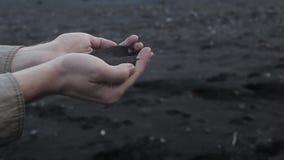 Island, schwarzer Sand Männer ` s Hände schließen oben, Handvoll des vulkanischen Sandes stock footage