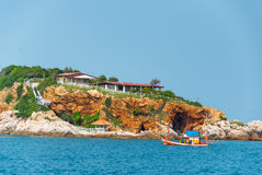 Island in the sea with small house and small boat driven Stock Images