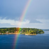 Island with settlement and rainbow in blue sky Royalty Free Stock Images