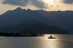 Island Shrine in Lake Kawaguchi. Sunset silhouette of the island shrine on lake Kawaguchi with mountains in the background Royalty Free Stock Images
