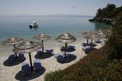 Island of Skopelos beach umbrelas. Beach with umbrellas and blue sun chairs in Skopelos island in Greece Stock Images