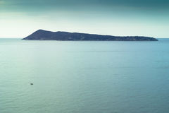 Island and small fishing boat on calm sea Stock Photography