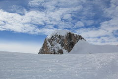 An island in the snow ocean. A big rock in the middle of the snow in austrian Alps Stock Images