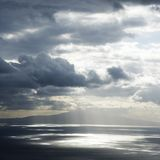 Island and sun through clouds. Royalty Free Stock Photo