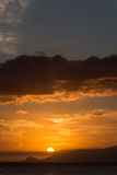 Island Sunset. Orange lit island sunset behind the clouds Royalty Free Stock Images