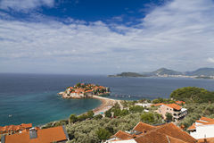 Island of Sveti Stefan in Montenegro. Island of Sveti Stefan at the Adriatic coast in Montenegro. It's red roofed old houses were used by pirates, now as a Stock Photos