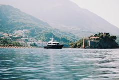 Island Sveti Stefan with a yacht nearby royalty free stock photography