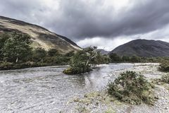 Island with tree in the middle of flowing stream.Scenic landscape of Lake District,Cumbria,Uk. Island with tree on the middle of stream flowing trough scenic royalty free stock images