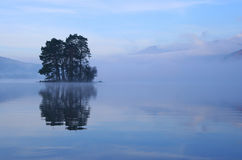 Island trees. Small tree-covered island rises out of the mist on Loch Tay, Perthshire, Scotland royalty free stock photography