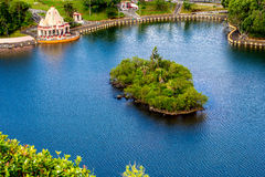 Island with tropical greenery in the blue lake Stock Images