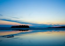 Island at twilight. A small wooded island silhouetted in a beautiful twilight sky Royalty Free Stock Images