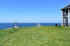 Island with two lighthouses from a viewpoint with grass, hut and bench. Isla Pancha, Ribadeo, Spain, sunny day. Illa Pancha, Ribadeo, Lugo Province, Galicia stock image