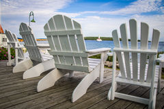 Island Vacation. Adirondack chairs line a wooden porch with the blue waters of Lake Huron and a lighthouse as the backdrop. Mackinaw Island, Michigan Stock Photos