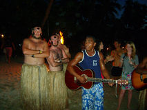 Islanders welcome. Men in straw skirts and guitar playing welcome to Fiji islands royalty free stock image