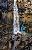 Islandia - una situaci?n del hombre joven delante de una cascada de Svartifoss imagenes de archivo