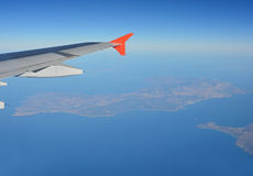 Islands below an aircraft wing Stock Photography