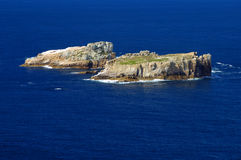 Islands in a deep blue sea. Two isolated and uninhabited rocky islands in the deep blue sea, off the coast of Tasmania, Australia. Space for text on the sea Stock Photography