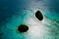 Islands and glittering sea. Two small islands in palau with sunshine glittering sea Royalty Free Stock Photography