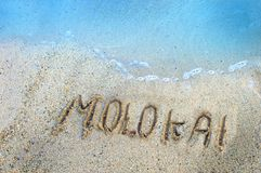 Islands in the Sand Molokai. Finger drawn letters withstand the gentle ebb and flow of the aqua waters of the Pacific Ocean surrounding the Hawaiian Islands stock photo