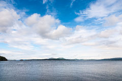 Islands under blue cloudy sky Royalty Free Stock Photography