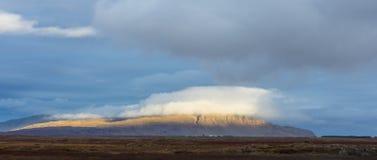 Islandzka góra zakrywająca w obłocznym i zaświecająca słońcem Fotografia Royalty Free