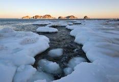 Islas en el invierno, mar frío en la puesta del sol Foto de archivo