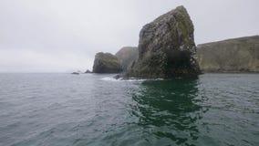 Islas rocosas hermosas con las montañas y los pájaros que vuelan en cielo nublado sobre paisaje de la agua de mar almacen de video