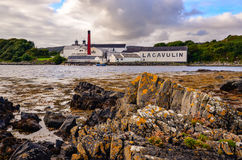 ISLAY, UNITED KINGDOM - 25 August 2013: Lagavulin distillery factory. With ocean coastline foreground, Islay, United Kingdom Royalty Free Stock Images