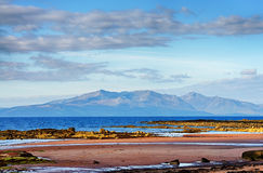 The Isle of Arran. Scenic view of the Isle of Arran pictured over the Firth of Clyde from the coast of West Kilbride in Scotland stock photos