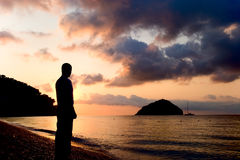 Isle or boat?. Silhouette of man watching isle and boat at the sunrise. Savona, Mediterranean sea Stock Photography