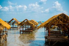 Isle. Gazebo by the river with a thatched roof.Cambodia. Island with houses made of straw near the river in Cambodia Stock Photography