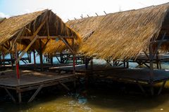 Isle. Gazebo by the river with a thatched roof.Cambodia. Island with houses made of straw near the river in Cambodia Royalty Free Stock Photos