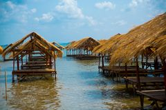 Isle. Gazebo by the river with a thatched roof.Cambodia. Island with houses made of straw near the river in Cambodia Royalty Free Stock Image