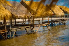 Isle. Gazebo by the river with a thatched roof.Cambodia. Island with houses made of straw near the river in Cambodia Royalty Free Stock Photo