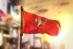 Isle of Man Flag Against City Blurred Background At Sunrise Back Stock Photos